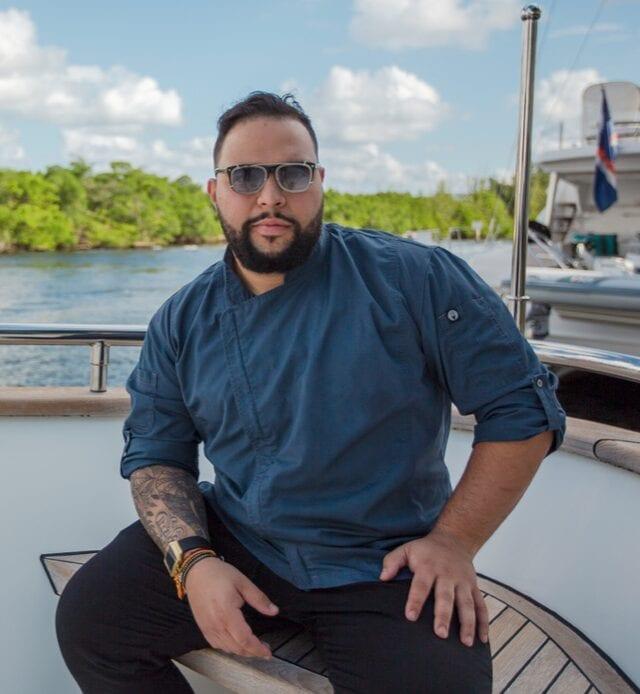 Superyacht chef Sergio Marichales sitting on a yacht in chef whites